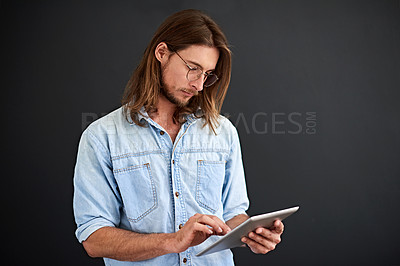 Buy stock photo Studio shot of a young man using a digital tablet against a gray background
