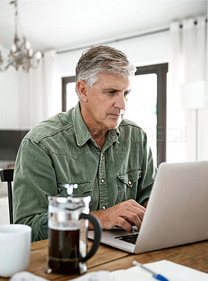Buy stock photo Cropped shot of a mature man working on his laptop at home
