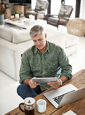 Buy stock photo Cropped shot of a mature man using a digital tablet and laptop at home