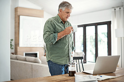 Buy stock photo Cropped shot of a mature man drinking coffee while working on his laptop at home