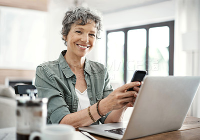 Buy stock photo Portrait of a mature woman sending an sms while working on her laptop at home