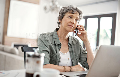 Buy stock photo Shot of a mature woman making a phonecall while working on her laptop at home