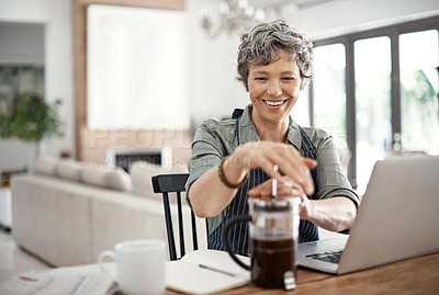 Buy stock photo Shot of a mature woman plunging coffee while workingon her laptop at home