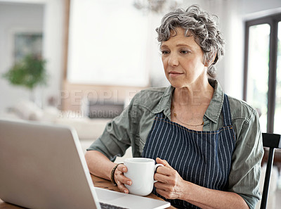 Buy stock photo Shot of a mature woman drinking coffee while working on her laptop at home