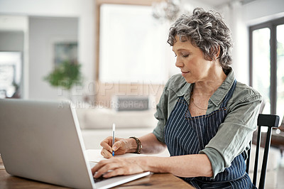 Buy stock photo Cropped shot of a mature woman working on her laptop at home