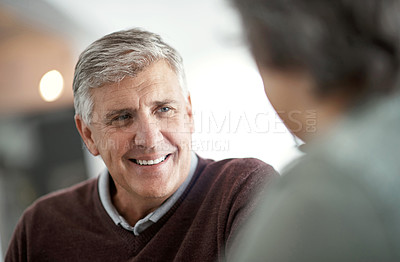 Buy stock photo Shot of a mature man having a conversation with someone blurred out in the foreground