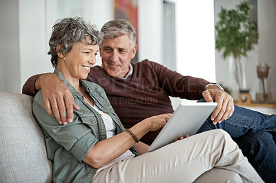 Buy stock photo Shot of a mature couple using a digital tablet while relaxing on their sofa