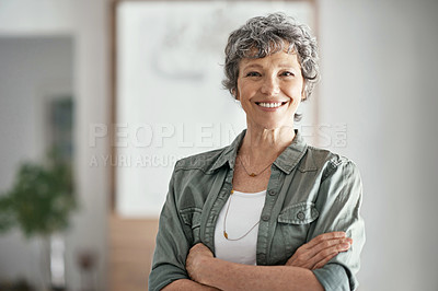 Buy stock photo Portrait of a mature woman smiling while standing with her arms folded in her home