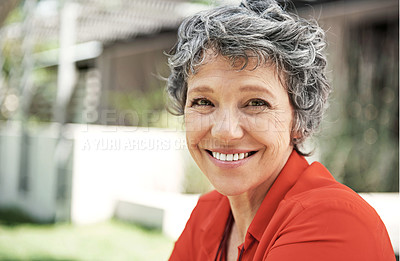 Buy stock photo Cropped shot of an attractive mature woman sitting in her garden on a summer's day