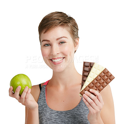 Buy stock photo Studio portrait of a fit young woman deciding whether to eat chocolate or an apple against a white background