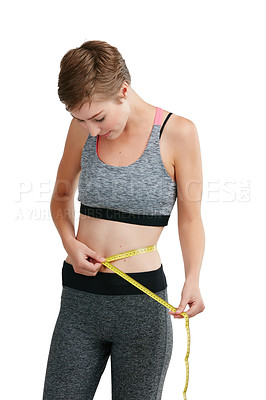 Buy stock photo Studio shot of a fit young woman measuring her waist against a white background