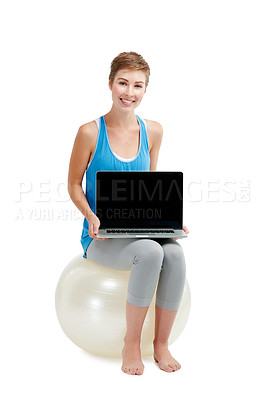 Buy stock photo Shot of a young woman holding a laptop while sitting on a exercise ball