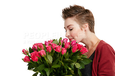 Buy stock photo Studio shot of a young woman smelling a bouquet of flowers against a white background