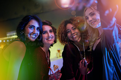 Buy stock photo Shot of a group of friends taking a selfie at a nightclub