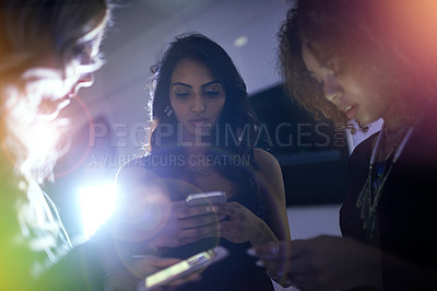 Buy stock photo Shot of a group of friends using their phones at a nightclub