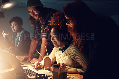 Buy stock photo Shot of a business team using a laptop together on a night shift at work
