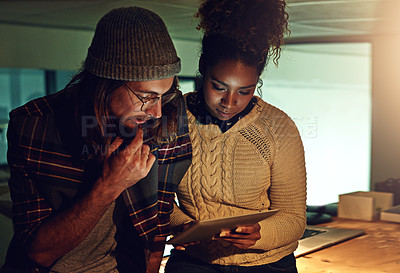 Buy stock photo Shot of two coworker discussing something on a digital tablet while working night shift at the office