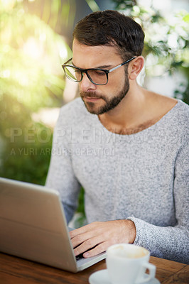 Buy stock photo Shot of a handsome young man using a laptop at an outdoor cafe