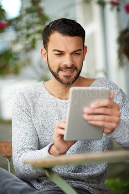 Buy stock photo Shot of a handsome young man using a digital tablet at an outdoor cafe