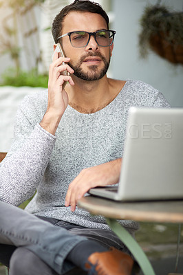 Buy stock photo Shot of a handsome young man using his phone and laptop at an outdoor cafe