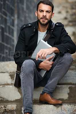 Buy stock photo Shot of a handsome young man sitting on urban steps and holding a laptop