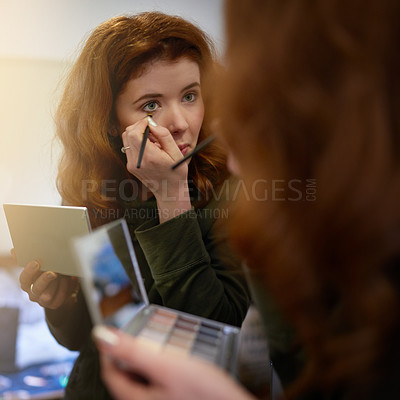 Buy stock photo Shot of an attractive young woman applying makeup in the mirror