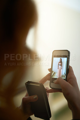 Buy stock photo Shot of an unrecognizable young woman looking at a photo on her cellphone