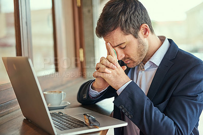 Buy stock photo Shot of a young businessman looking stressed while sitting in a coffee shop