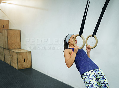 Buy stock photo Shot of a young woman working out with rings at a gym