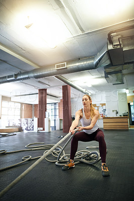 Buy stock photo Shot of a young woman working out with ropes at a gym