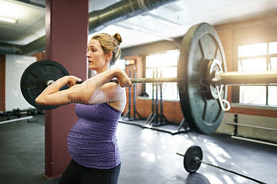 Buy stock photo Shot of a pregnant young woman working out with a barbell at a gym