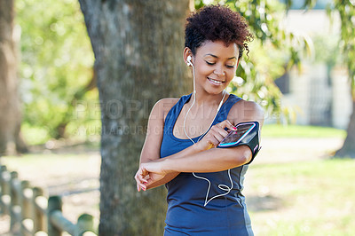 Buy stock photo Cropped shot of a sporty young woman checking her playlist before a run