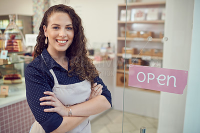 Buy stock photo Portrait of a young woman standing by the door of her cake shop