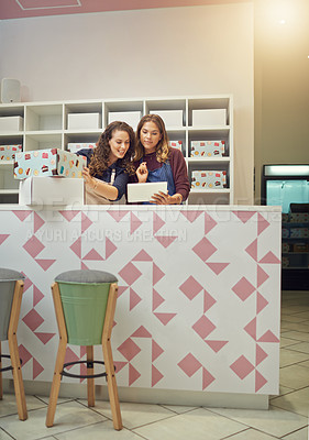 Buy stock photo Shot of two young women working with wireless technology in their bakery