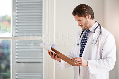 Buy stock photo Cropped shot of a doctor looking at notes on a clipboard in a hospital