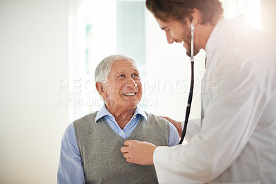 Buy stock photo Cropped shot of a doctor using a stethoscope to examine his senior patient in a clinic