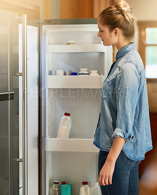 Buy stock photo Cropped shot of a young woman looking inside her fridge at home