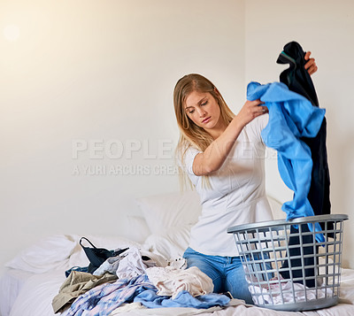 Buy stock photo Cropped shot of a young woman sorting through some laundry at home