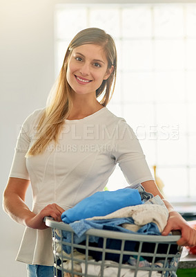 Buy stock photo Portrait of a young woman holding a basket of laundry