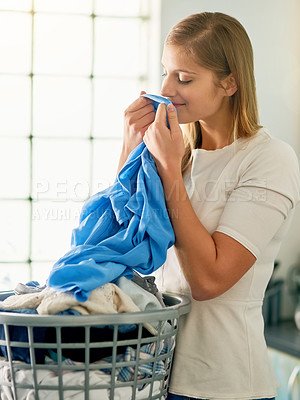 Buy stock photo Cropped shot of a young woman smelling fresh laundry