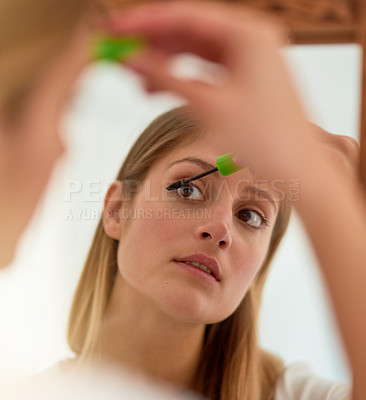 Buy stock photo Shot of a young woman applying mascara in front of a mirror at home