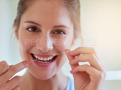 Buy stock photo Portrait of a young woman flossing her teeth in a bathroom
