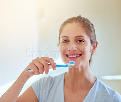 Buy stock photo Portrait of a young woman brushing her teeth in a bathroom