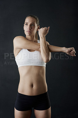 Buy stock photo Studio shot of an attractive young woman warming up against a dark background