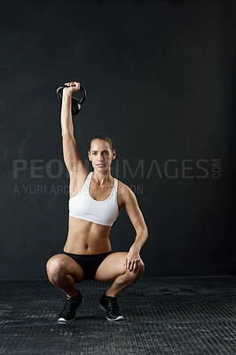 Buy stock photo Studio portrait of an attractive young woman working out with a kettle bell against a dark background