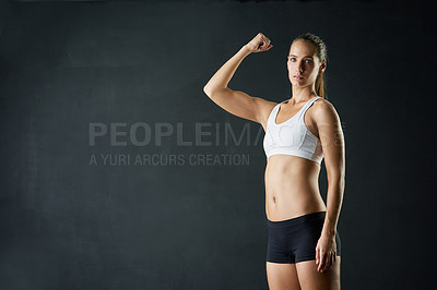 Buy stock photo Studio portrait of an attractive young woman felxing her bicep against a dark background