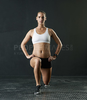 Buy stock photo Studio portrait of an attractive young woman doing lunges against a dark background