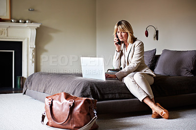 Buy stock photo Shot of a mature businesswoman sitting on a hotel bed talking on her cellphone and using a laptop