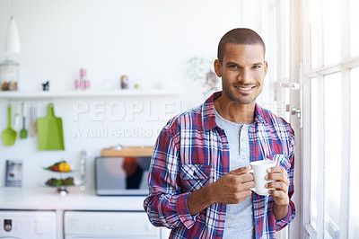 Buy stock photo Portrait of a smiling young man standing by his kitchen window drinking a coffee