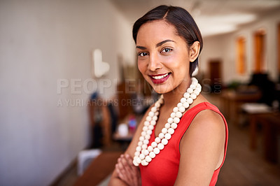 Buy stock photo Portrait of a smiling young woman standing with her arms crossed in an office